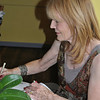 "Artist and author Susan McLaughlin of Newtown signs a copy of her book, Depingo Ergo Sum, on Sunday, October 2, during the opening of her art show at The Good News Café in Woodbury. The art show, also entitled ""Depingo Ergo Sum (I Paint, Therefore I Am),"" features Ms McLaughlin's large acrylic paintings in the main dining room, and her illustrations, cartoons, and magazine covers in the ""radio room"" of the café. The show runs through Tuesday, November 29.  (Crevier photo)"