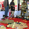 Junior firefighter Andy DeWolfe, on the right, answered questions about the gear used in different situations at the gear try-on station. The Holden family, including young siblings Allison and Matthew, were among the event's visitors with plenty of questions.  (Hicks photo)