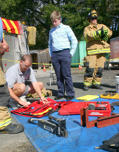 First Assistant Chief Kevin Stoyak, kneeling, explains to John Locke some of the equipment firefighters set out when responding to a motor vehicle accident. On the right, Karl Sieling, Jr, prepares to participate in one of the afternoon's demonstrations, when firefighters used spreaders to pry open a car door.(Hicks photo)