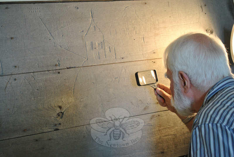 Newtown Town Historian Dan Cruson takes a close look at recently discovered folk art panels. The chestnut boards, inscribed with a fictional village scene, date from the late 19th Century, he guesses, and were likely carved by a preteen or teenage boy.  (Crevier photo)