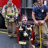Ross Janutolo, left, and Ray Corbo, right, of Newtown Hook & Ladder visited Hawley Elementary School on Friday, October 14, with other members of Newtown Hook & Ladder who explained fire safety tips and more to Hawley students. Center, Joseph Corbo, Ray's son and a Hawley student, helped the firefighters explain different aspects of a firefighter's duties.  (Hallabeck photo)