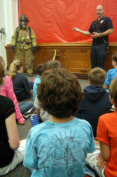 Joe Miller, right, and Rick Camejo of Newtown Hook & Ladder described what it is like to wear turnout gear, as worn by Mr Camejo in the photo, to students in Hawley Elementary School's multipurpose room last Friday. (Hallabeck photo)