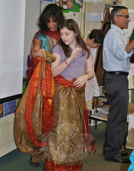 Monju Kapur expertly drapes RIS sixth grade student Tara Gaiser in five meters (more than 16 feet) of material to make a sari, the traditional wear of women in India. It is an exciting moment, Ms Kapur told the class, when a girl gets to wear a sari for the first time.  (Crevier photo)
