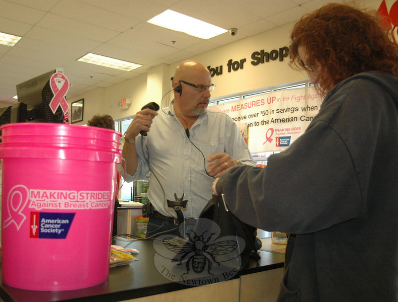 Manager Steve Zvon checks out a customer beside one of the many huge pink buckets positioned throughout the store. Newtown's Ace Hardware on Church Hill Road at Queen Street has teamed up with the American Cancer Society and 70 regional Ace retailers in the fight against breast cancer this October, National Breast Cancer Awareness Month. Customers are encouraged to toss donations into the buckets, which will be pooled and donated to the cause.  (Voket photo)