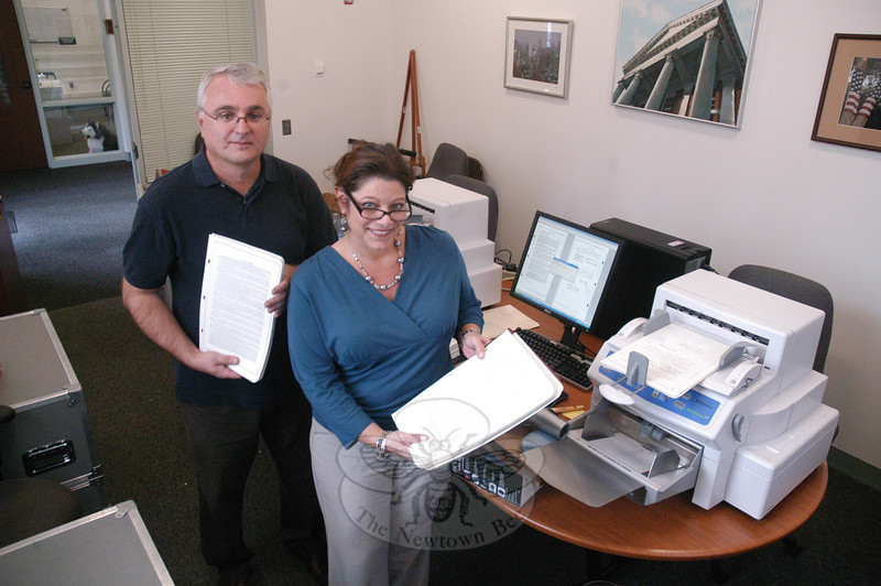 Town Clerk Debbie Aurelia and computer technician Branko Hrnjak of Cott Systems, Inc, are shown in a conference room at Newtown Municipal Center on October 20, where Mr Hrnjak was in the process of digitally copying thousands of pages of local land records for inclusion in the town's in-house computer network. In the future, the town's land records will be posted on the Internet and title searchers will be able to remotely to gain access to such data for a fee.  (Gorosko photo)