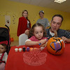 Ten-month-old Paige Keane watches from her stroller while her sister Alexis and their father David Keane paint a pumpkin in Kiddie Land at The Garage last weekend when the Newtown Police Explorers held a Halloween party.  (Bobowick photo)