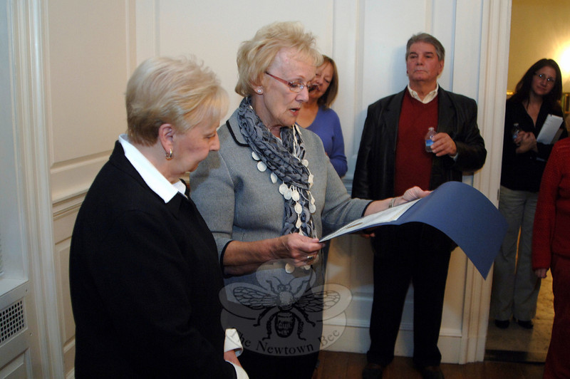 First Selectman Pat Llodra reads from a certificate honoring the retiring Sandra Motyka, left. (Bobowick photo)