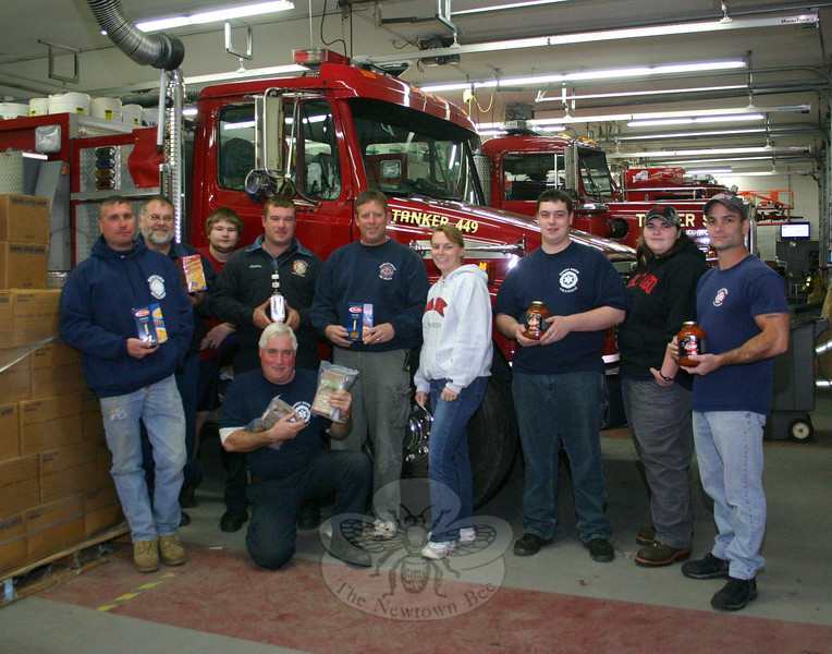 "Just in time for Thanksgiving, firefighters from all five of Newtown's volunteer companies will accept food and cash donations for FAITH Food Pantry. On Saturday, November 19, from 9 am until 1:45 pm, members of Botsford and Dodgingtown fire companies will be set up outside Stop & Shop in Sand Hill Plaza on South Main Street. During the same time frame, members of Hawleyville, Hook & Ladder, and Sandy Hook will be outside Big Y on Queen Street. All donations will be delivered to the Sandy Hook-based food pantry that af-ternoon. Getting ready to receive donations this week were, from left, Hook & Ladder mem-ber Rob Manna; Karl Sieling and Ryan Piccirillo from Sandy Hook; Brian Slattery, Hook & Ladder; Don ""The Rebel"" Hutchins,"" Hawleyville; event coordinator Karin Halstead, Andy Ryan, and Erika Knapp, all of Sandy Hook; and Ray Corbo, Hook & Ladder. George Lock-wood Jr, another member of Sandy Hook, is kneeling in front.  (Hicks photo)"