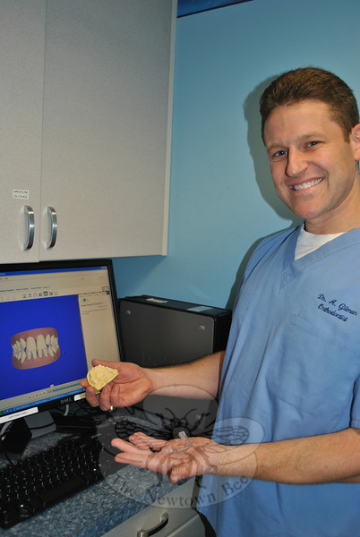 Dr Aaron Gilman, orthodontist with Dental Associates, holds a cast model of a patient's mouth in his right hand. The digital image on the screen behind him is produced by the new iTero digital scanner, installed in the Newtown office November 8, which practically eliminates the need for cast molds for the orthodontist's Invisalign brand customers. Precisely calculated templates of the teeth, like the one in Dr Gilman's left hand, are created through the digital imagery.  (Crevier photo)