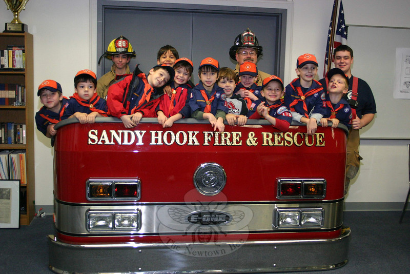 "Members of Newtown Boy Scout Pack 170, Cub Scouts in Dens 1 and 3, visited Sandy Hook Fire & Rescue's main station on Monday, November 7, where they met members of the volunteer fire company and learned about some of the gear and tools firefighters use. The boys, along with parents and a few siblings, spent some time in the company's meeting room, where this photo was taken, being reminded about the ""Stop, Drop & Roll"" rule and other safety lessons. Then they headed into the station's bays and were allowed to climb into an engine and a rescue vehicle.	 (Hicks photo)"