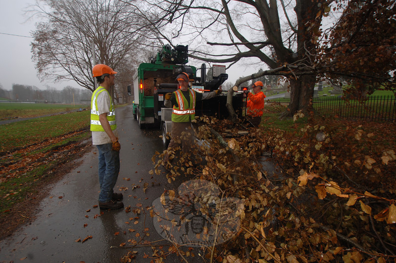 A crew from Newtown Arbor Service was able to finish clearing debris near the intersection of Deep Brook Road and Elm Drive on Wednesday despite an early afternoon rain. The crew is one of many tasked with picking up piles of storm debris following the October 29 nor'easter. From left is Willie Provey, John McGrath, and Paul Hubina.  (Bobowick photo)