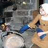 Amelia Schill, 12, cooked onions over coals in an iron skillet during open hearth cooking demonstrations held at the Matthew Curtiss House on Sunday, November 13, sponsored by the Newtown Historical Society. Visitors to the house were offered tours, apple cider, and, when ready, vegetable stew during the event.  (Hallabeck photo)