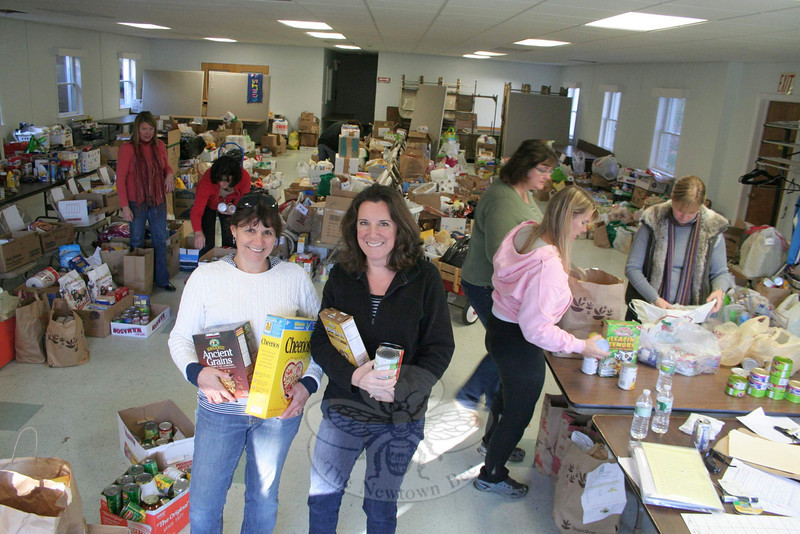 Mandy Monaco, left, and Cyndy DaSilva stand in the midst of volunteer activity on November 18, when Women Involved in Newtown (WIN) received, organized, and then delivered donations of food and other items that will help 70 Newtown families put meals on their tables for Thanksgiving and into the holiday season. The culmination of the WIN Thanksgiving Basket Program took place in the meeting room of Newtown United Methodist Church.  (Hicks photo)