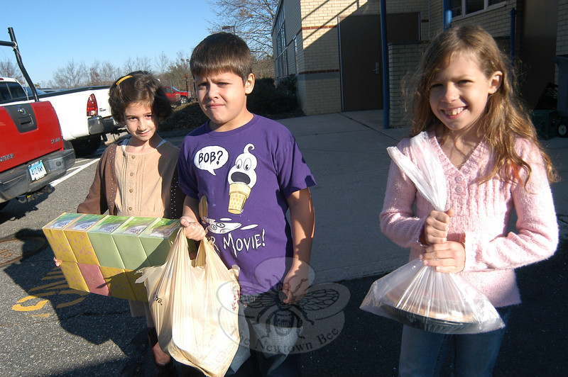 Middle Gate Elementary School students, from right, Mary Sortino, Sean Gordon, and Claudia Sorrentino helped load food collected at their school for Women Involved in Newtown's Thanksgiving Baskets program on Friday, November 18. A number of schools helped WIN with their annual holiday program.  (Hallabeck photo)