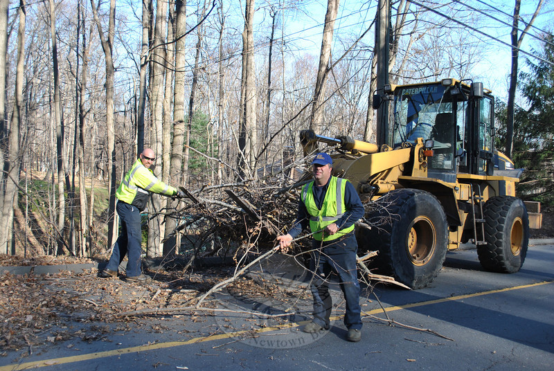 Newtown Highway Department employees Chris Capozziello, right, and Robert Toth pick up stray branches falling from the wheel loader, Monday, November 21, on Scudder Road. They are among the Public Works employees working to rid the streets of storm debris before winter sets in.  (Crevier photo)