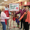 Anna Wiedemann and Steve Bennett, on the left, have taken over the coordination efforts of bell ringers for the Newtown chapter of The Salvation Army from Sylvia Poulin, second from right, and Marie Sturdevant, on the right. Sneaking the first donation of the year into the red Salvation Army bucket is Mrs Sturdevant's grandson, Cullan Sturdevant.  (Hicks photo)