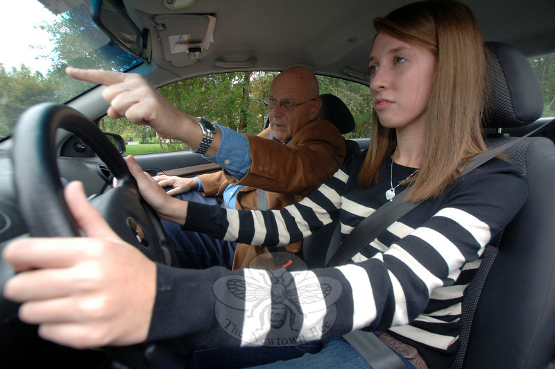Driving school owner Gary Knepler instructs Newtown student Anna Dilworth as part of her recent behind-the-wheel training. Mr Knepler along with his father, Simon, and his son, Howard, represent three generations of a family dedicated to and recognized internationally for excellence and a commitment to driving safety.  (Bobowick photo)
