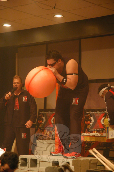 One of the several strongmen with the evangelical Xtreme Impact group who performed at Grace Christian Fellowship on November 18 uses the sheer force of his lungs to blow up a hot water bottle.  (Gorosko photo)