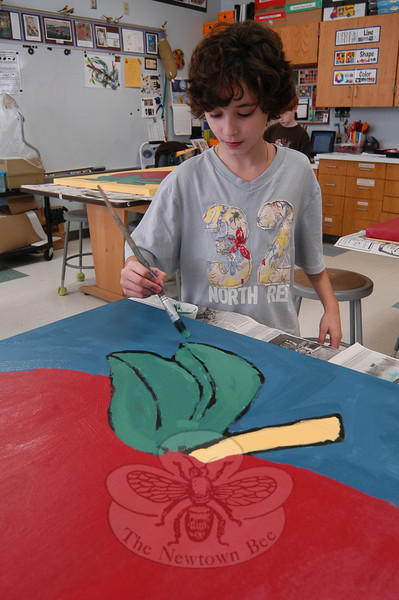 Hawley fourth grade student Evan Camputo worked on painting one of the canvases on Monday, November 21, that will go on display in the school's Mary Hawley Café when completed.  (Hallabeck photo)