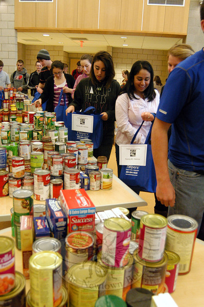 Newtown High School students assembled bags of food collected through a food drive at the school that will go to local families through the Women's Center of Greater Danbury and the food pantry at Social Services in Newtown.  (Hallabeck photo)