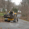 Continued clearing efforts to remove storm debris now include a skid steer rented by Public Works, which makes quick work of piled limbs. Town crew members Anthony Capozziello, Joe Pra and Rob Toth cleared limbs stacked curbside on Pleasant Hill Road Tuesday. The small machine is lighter on residents' lawns, more maneuverable, and reduces the amount of labor and ma-chinery needed to cart and clear debris. Driving the skid steer, Mr Capozziello grabs a bundle of downed wood.  (Bobowick photo)