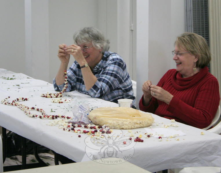 Vicky Boccuzzi, on the left, concentrating on her string of popcorn and cranberries, and Bonnie Johnson spent part of their Tuesday afternoon at Newtown Meeting House. The ladies, members of The Garden Club of Newtown, were among those working on final touches for this weekend's Annual Garden Club Greens Sale.  (Hicks photo)