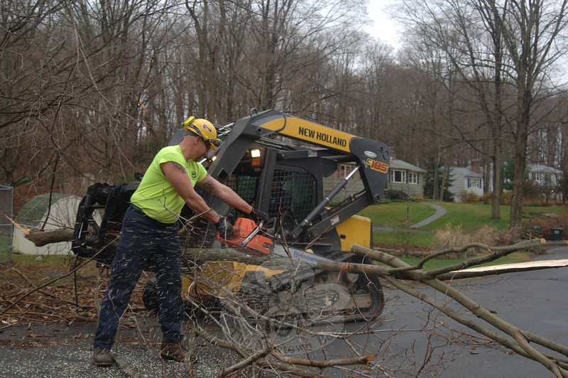 Rob Toth cuts apart lengthy limbs Tuesday while his crew works on Pleasant Hill Road in Dodgingtown.  (Bobowick photo)