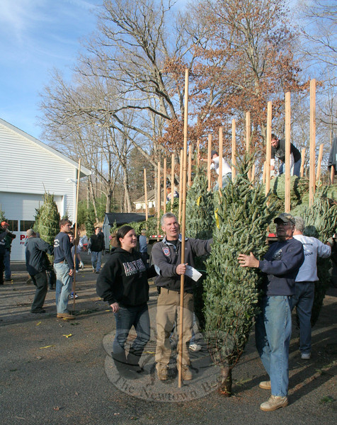 Kelly Burton, left, and her dad Mike, center, are the co-chairs of the Christmas Tree & Holiday Fundraiser for Sandy Hook Volunteer Fire & Rescue. When trees arrive in Sandy Hook they are unloaded by members of the fire company and organized by height and type. On the right, holding one of the trees fresh off the truck from Vermont to be measured by Mr Burton, is Sandy Hook Co. member Ray Wisniewski.  (Hicks photo)