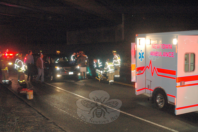 Police, fire, and ambulance crews prepare to transport a victim of a rear-end collision that occurred December 5 at about 6:22 pm on Route 34 near the intersection of Wasserman Way. The crash resulted in an injury to Jennifer Foss of Spring Trail, Sandy Hook, who was transported to Danbury Hospital because of reported back pain. According to police, Aaron Coopersmith, 28, of Taunton Hill Road was operating a 2009 Subaru Forester southbound under the Interstate 84 Exit 11 overpass when he struck Foss's 2011 Acura MDX, which had come to a stop in heavy traffic. Coopersmith was issued an infraction for following too closely.  (Voket photo)