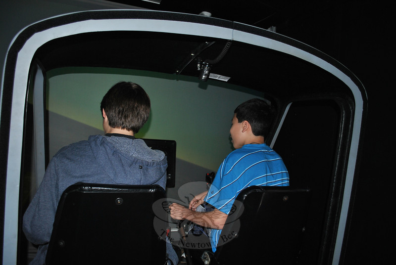 Zachary Mangold, left, and Scott Dakofsky, handle the controls inside the helicopter flight simulator at Fraser-Woods Montessori School, Monday, December 5. Scott's stepfather, Mark Simoneau, owner of Helitek, which leases flight simulators to training schools, brought the high tech learning tool to the school as part of Scott's internship on rotor crafts.  (Crevier photo)