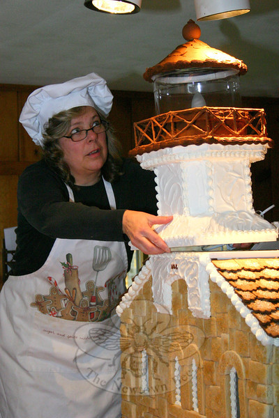 Donna Ball prepared to -- carefully! -- place the beacon on top of Sugar Cookie Sheffield Island, which she and fellow Newtown resident Laura McNamara created for The Maritime Aquarium's 2011 Festival of Lighthouses.  (Hicks photo)