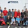 Far left, Mark and LaDonna Simoneau and 9-year-old daughter Stephanie join Fraser-Woods Montessori School eighth grade students outside of the trailer housing the helicopter flight simulator. Front row, kneeling, are Priyanka Agadi, Elizabeth Sankey, Tucker Kestner, Scott Dakofsky, and Adam Padilla. Back row, next to Mr Simoneau, are William Mitchell, Mai Lemeur, Cole Lee Rogalin, Jesse Kendler, Megan Hickey, James Stiles, Andrew Waltzer, and Zachary Mangold.  (Crevier photo)