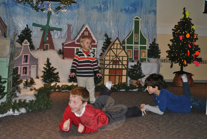 Children from Trinity Episcopal Church crawl past the Dutch Village, set up each year as part of the St Nicholas celebration.  (Crevier photo)