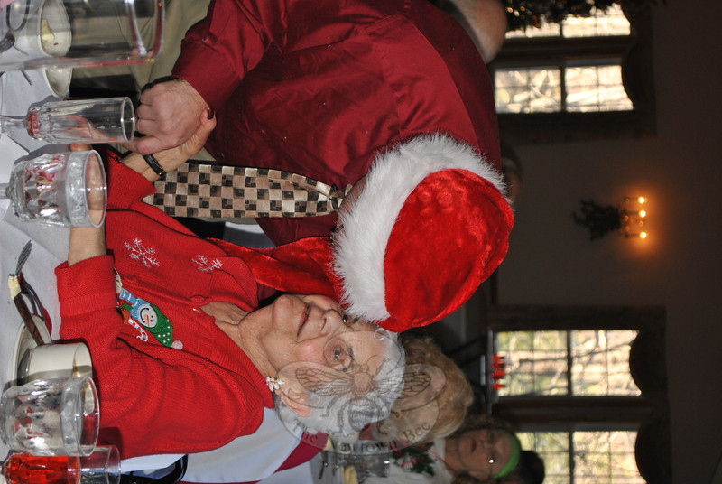"""Santa"" Kevin Parker gives Newtown Senior Center member Florence DePalma a hug and a kiss, as he makes his way from table to table during the Tuesday afternoon holiday party at Capellaro's Grove in Bethel.  (Crevier photo)"