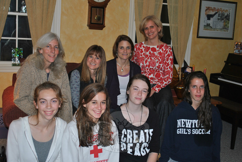 Members of a mother-daughter book club that has met for eight years face a bittersweet final year together as the young women, all seniors in high school, prepare to launch into life after graduation in the spring. Pictured from left, front row, are Katie Burns, Quincy DeYoung, Nicole Lang, and Cassie Fallon. Seated behind them, also from left, are mothers Sarah Burns, Suzy DeYoung, Suzanne Lang, and Valerie Fallon.  (Crevier photo)
