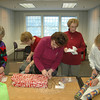 "Volunteers from the Newtown Woman's Club converged at the Booth Library community room December 13 to wrap a generous assortment of gifts for a local family ""adopted"" through the Newtown Fund's Holiday Basket Program. The wrap artists for this activity included, from left, Milda Kolesar, activity chair Pat McCarthy, Ann Kirk, Marge Cassin, and Jean Swanhill. They were joined by Joyce Webster, JoAnn Bruno, Alice Horahan, Louise Begley, Debbie Stakel, and Shirley Ferris.  (Voket photo)"