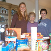 Julia Trudell, left, and her younger sister Haley with their grandmother, Rosemary Trudell, went door to door on Saturday, December 10, to collect gifts donated by residents of Walnut Tree Village, where Mrs Trudell is a resident. The toys and clothes collected for The Newtown Fund's annual Depot Day were delivered to Newtown Youth & Family Services.  (Hallabeck photo)