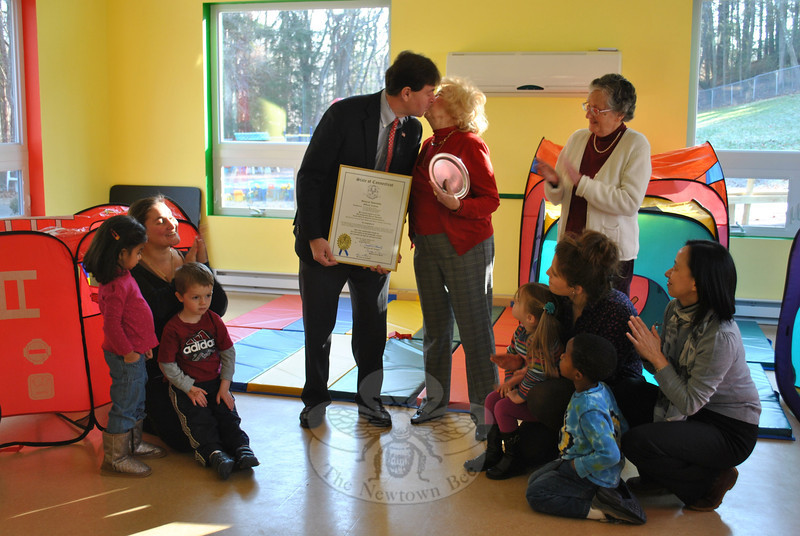 """You have earned it,"" says Connecticut Senator Andrew Roraback, presenting Children Ad-venture Center's Chairman Mae Schmidle with an official citation — and a smooch — at a brief ceremony, Wednesday, December 14, at the school on Riverside Road. The citation was awarded by the State General Assembly in honor of the new playground and Sunshine Room addition dedicated to Ms Schmidle earlier this fall, and in honor of Ms Schmidle's years of contributions to the school. Looking on is CAC Vice Chairman Barbara Borst, and kneeling, from left, teachers and CAC children Vevika Menon, 3, Anna Ruggiero (Explorers teacher), Layne Sachreiter, 4; Addison Cordova, 3, Noel DeLorenzo (Adventure teacher), Asher Williams, 4, and CAC bookkeeper Jing Hu.  (Crevier photo)"