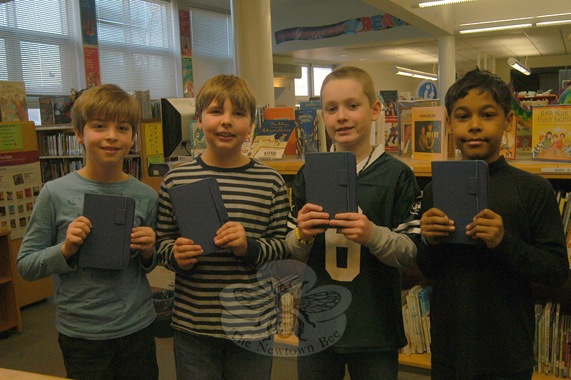 Sandy Hook School fourth graders, from left, Colton Procaccini, Henry Wishneski, Devin O'Connell, and Emmanuel Wilford were the first students to take out Amazon Kindles from their school's library on Monday, December 12.  (Hallabeck photo)