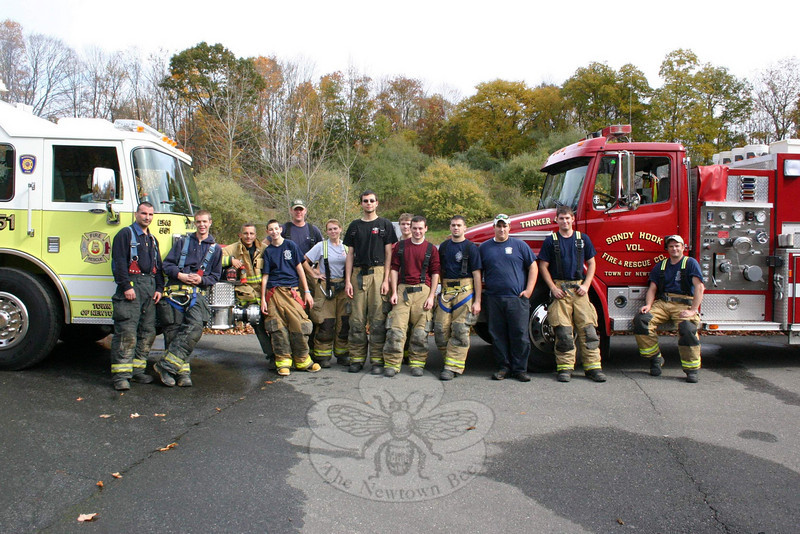 Members of all five of Newtown's volunteer fire companies recently spent a Sunday working together during a drill on Riverside Road. On Saturday, November 20, all five companies will once more work together for the annual Fill The Fire Truck Food Drive, again being coordinated by Sandy Hook EMT Captain Karin Halstead, sixth from left. From 9 am until 2 pm, members of Sandy Hook, Hawleyville and Hook & Ladder will be at The Big Y on Queen Street, while members of Botsford and Dodgingtown will be in front of Stop & Shop in Sand Hill Plaza, 228 South Main Street. Both locations will serve as drop-off points for food, money, and gift cards of any value. At the end of the collection hours, all donations will be delivered to FAITH Food Pantry in Sandy Hook.  (Hicks photo)