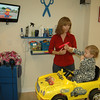 Two-year-old Reinna points to her favorite TV character from the Fun Kuts race car chair while stylist Janet Merrifield gets ready to provide a quick trim. Each of the salon's five stations has its own 19-inch television to help clients pass the time while they visit.  (Voket photo)