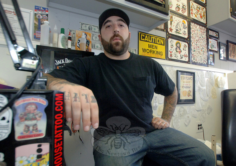 Hat City Tattoo artist and shop owner Chris Tavino sits surrounded by his handiwork at the Danbury shop.  (Bobowick photo)