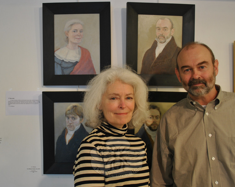 For this fall's Reflectionist show, artist Jennie K. Williams of Newtown experimented with the American primitive style, imposing her family member's heads onto previously painted busts in early American clothing. Her husband, Brian, stands with Ms Williams and the paintings, which include her sons, Tom and Michael.  (Crevier photo)