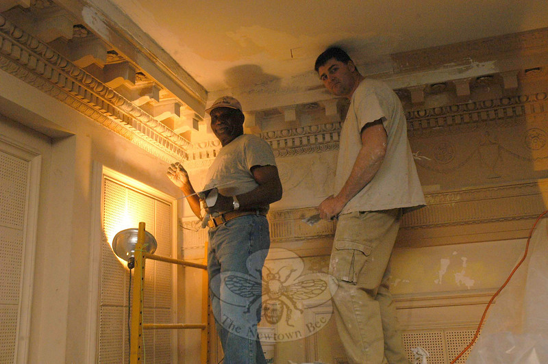 Cecil Watson, left, and David Massey, both of Kronenberger & Sons Restoration, Inc, of Middletown, made some plaster repairs on December 19 on the balcony area of the theater in Edmond Town Hall. The firm specializes in returning historic structures to period accuracy.  (Gorosko photo)