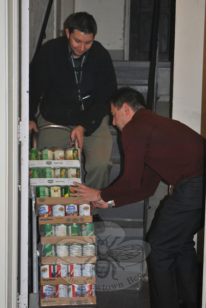 Caraluzzi's Newtown Market CEO Mark Caraluzzi steadies the cans as Grocery Manager Joe Brown trucks cases of donated goods down into the basement of St John's Episcopal Church, where FAITH Food Pantry is located. (Crevier photo)