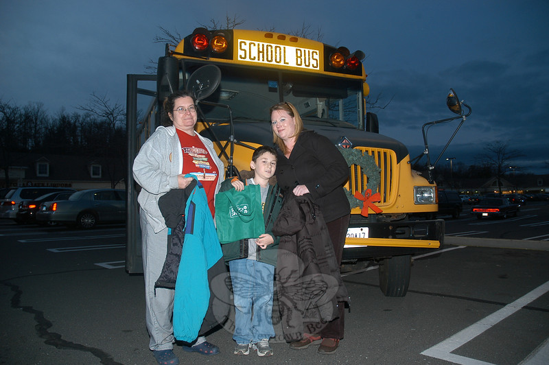 A school was positioned at the Stop & Shop supermarket parking lot at Sand Hill Plaza on the evening of December 16, and during the day on December 17, as part of a collection of winter outerwear and nonperishable food items for Newtown Social Services. Local school bus owner-operators conducted the collection project. Shown from left are LeReine Frampton, Tanner Genc, and Kristie Genc.  (Gorosko photo)