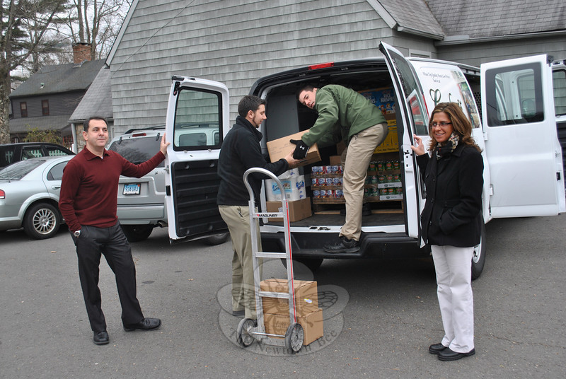 Mark Caraluzzi, CEO of Caraluzzi's Markets, and Jen Caraluzzi-Dimyan hold the van doors as Paul Mariani, assistant store manager, hands the first of several cases of donated items to Joseph Brown, manager of Caraluzzi's Newtown Market. The Newtown market donated two pallets of canned goods and paper goods to FAITH Food Pantry on Tuesday, December 20, after realizing the increased need at the local pantry.  (Crevier photo)