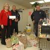 The Taunton Press, Inc, and its employees have made holiday season donations of food and money to the local chapter of the Salvation Army and the Newtown Social Services Department to make the holidays brighter for the needy. Shown with some of the food items collected are Ann Piccini, town director of Social Services, and Pete Daccolti and Dave Ferraro. Messrs Daccolti and Ferraro, both of the town Public Works Department,  helped transport the food items from The Taunton Press to the town food pantry at Town Hall South.  (Gorosko photo)
