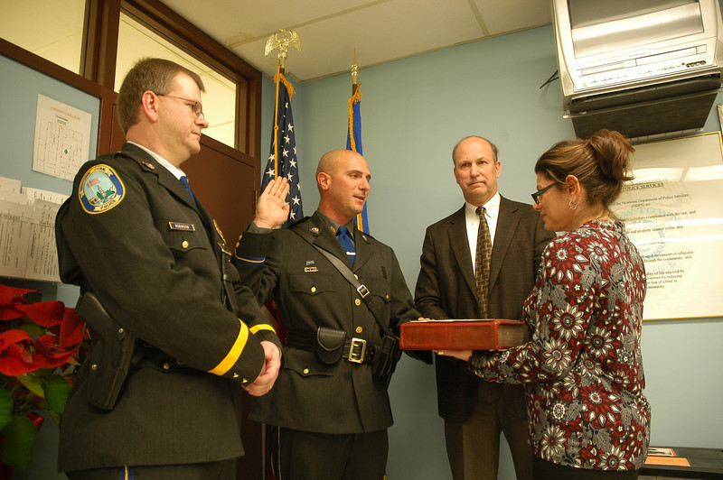 Police Lieutenant Richard Robinson, left, looks on as Sergeant Steven Santucci takes the oath of office from Town Clerk Debbie Aurelia on Tuesday, January 3, at the police station. Looking on is Police Chief Michael Kehoe. Lt Robinson and Sgt Santucci took the oaths of office in ceremonies recognizing their police promotions.             — Bee Photo, Gorosko
