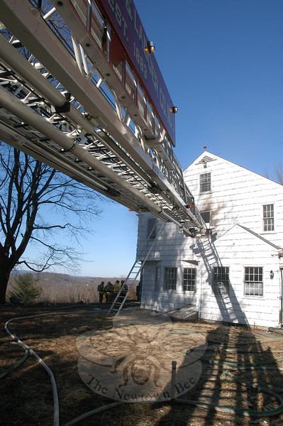 Newtown Hook & Ladder's aerial ladder is extended toward a vacant house on Mt Pleasant Road where all five local volunteer fire companies practiced putting out structure fires on January 28. —Bee Photo, Gorosko
